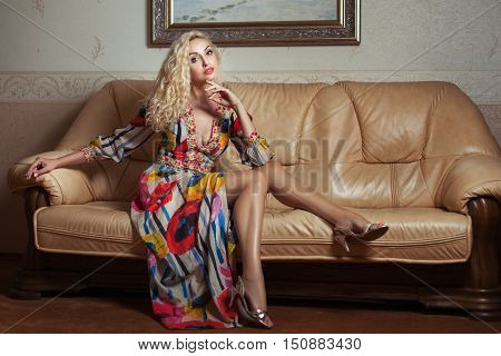 The room beautiful young blonde woman sitting on a leather couch.