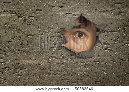 Eye looking through a hole in a wall.