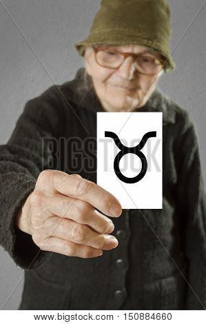 Elderly woman holding card with printed horoscope Taurus sign. Selective focus on card and fingers.