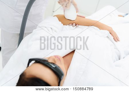 Young woman is getting ultrasound skin care treatment. She is lying with enjoyment. Beautician is pampering her arm by equipment