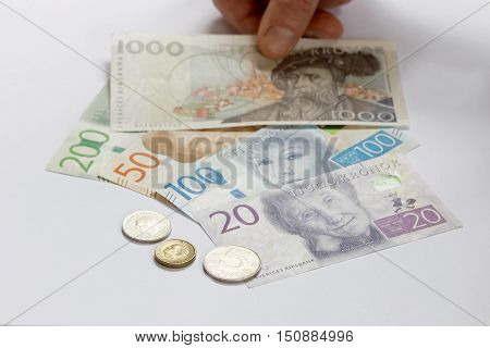 Swedish currency 1 5 10 20 50 100 200 and 1000 SEK new layout 2016 laying on a table and a hand