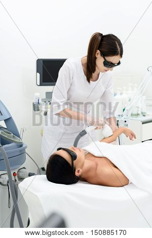 Concentrated beautician is massaging female arm by ultrasound regeneration equipment. She is standing in her office at wellness center