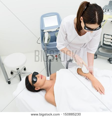 Healthy young woman is lying and relaxing on massage table in beauty salon. Beautician is pampering her hand by laser skincare equipment with concentration. They are wearing protective glasses
