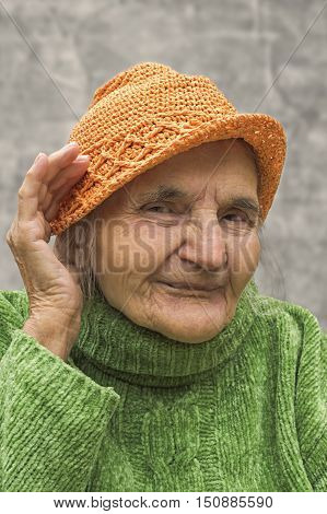 Elderly woman holding hand close to an ear. Hearing problems.