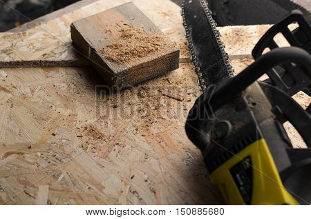 Chainsaw With Sawdust And Pieces Of Wood.