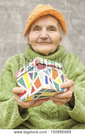 Elderly woman holding a gift box. Selective focus on gift.