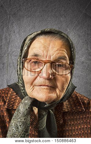 Portrait of an old woman on a vintage background dreaming the past. Soft focus.