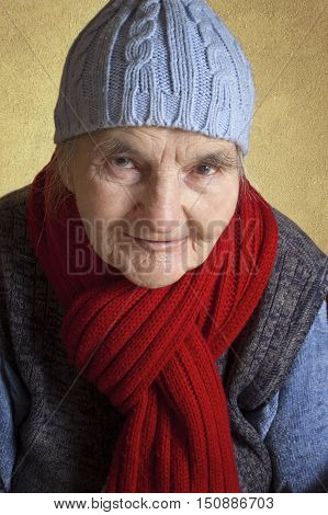 Portrait of a smiling elderly woman with blue cap and red scarf.