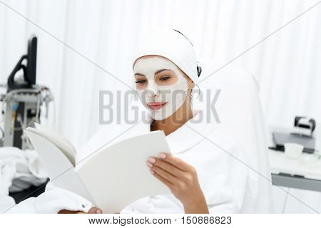 Healthy girl is resting at beauty salon. She is sitting in bathrobe and reading magazine with interest. Lady has clay mask over her face