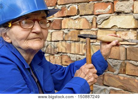 Elderly woman holding a hammer and chisel. Construction background