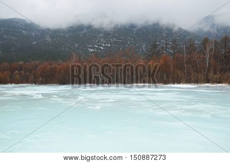 Icebound river on a cloudy spring day. Irkutsk Region, Russia