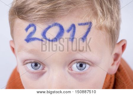 Numeral 2017 on the forehead of a young boy new year