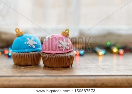 Two Christmas decorated cupcakes on wooden windowsill