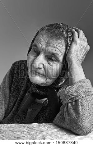 Portrait of sad lonely pensive old senior woman. Dreaming the past.
