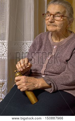 Portrait of an old woman with grinder in hands. Dreaming the past.
