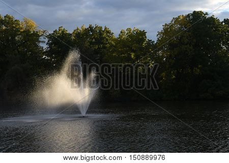 Fountain, back-lit, backdrop, bright, mist, left-aligned, with trees
