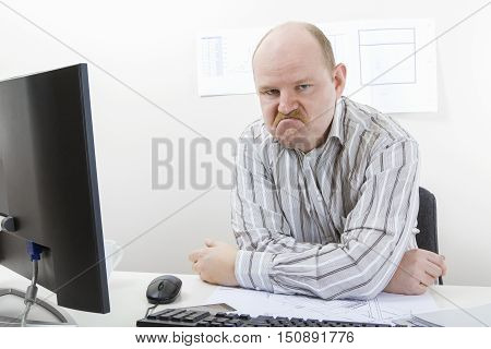 Portrait of angry mature businessman sitting at desk in office