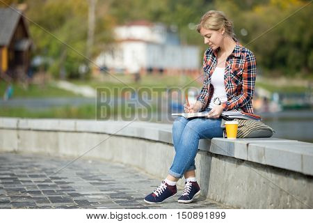 Portrait of a young attractive student girl sitting at the bridge her legs crossed, writing, coffee near, waterline behind. Back to school concept photo, lifestyle