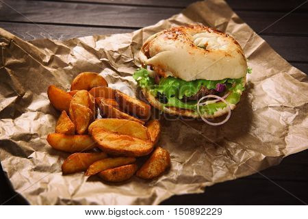 Hamburger And Potato Wedges On Wooden Table