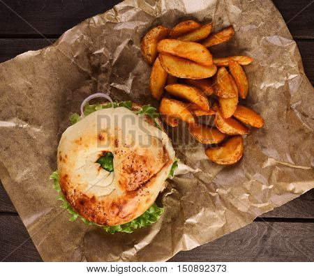 Burger And Potato Wedges On Wooden Table