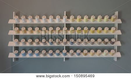 In front of multicolor bobbin storage on the wall