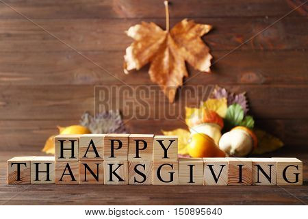 Wooden cubes with inscription HAPPY THANKSGIVING on blurred background. Thanksgiving day concept