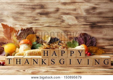 Autumn composition of vegetables, leaves and cubes with inscription HAPPY THANKSGIVING on wooden background. Thanksgiving day concept