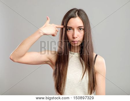 Teenage woman committing suicide with finger gun gesture isolated on gray
