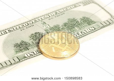 Golden bitcoin coin and one hundred dollar banknote isolated on white