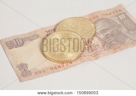 Golden bitcoin coins on Indian Ten Rupee on white background