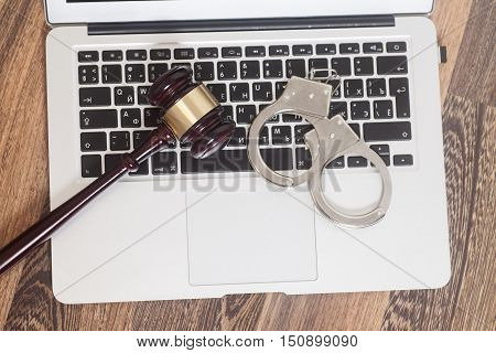 Handcuffs and gavel on laptop on wooden background