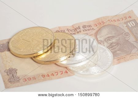 Golden and silver bitcoin coins on Indian Ten Rupee on white background