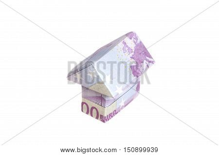 Origami house made of 500 euro banknotes on white background