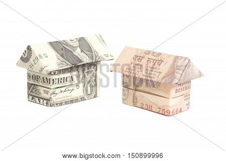 Origami house made of 100 dollar and Indian rupee banknotes isolated on white background