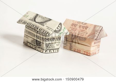Origami house made of 1 dollar and Indian rupee banknotes on white background