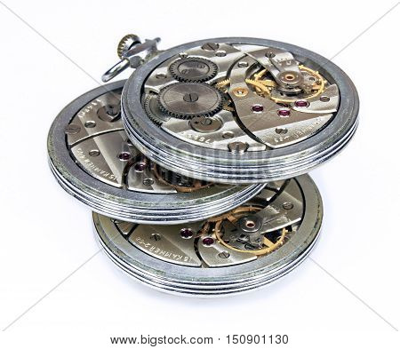 Three similar old soviet pocket watch mechanism with wheels and springs isolated on white background