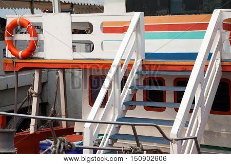 Colorful wooden boat deck with life buoy. Happy ship cruise background. Orange blue and white colors