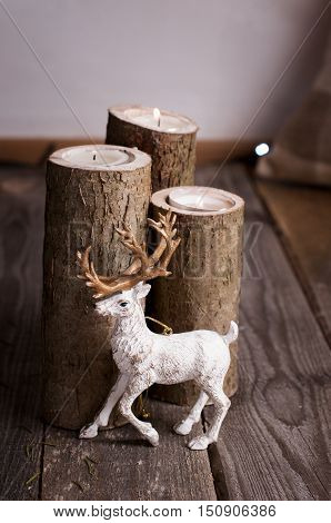 Stylish Christmas decor - deer near burning candles in wooden candlesticks