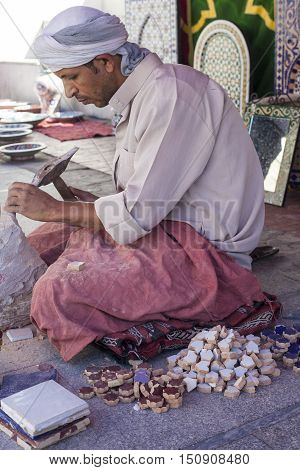 Badajoz Spain - September 24 2016: Artisan makes pieces for mosaic craftwork. He is shaping pieces from glazed tiles