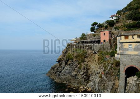 Riomaggiore Italy - September 4 2016: Buildings on rock at sea in Riomaggiore city in Liguria Italy. One of five Cinque Terre cities (unesco world heritage). Unidentified people visible.