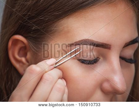 Master makeup corrects and gives shape to pull out with forceps previously painted with henna eyebrows in a beauty salon. Professional care for face