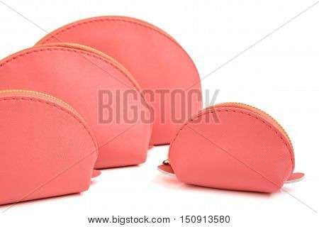 Selective focus on a small pink round bags - pink cosmetic bags collection in four size isolated object on white background