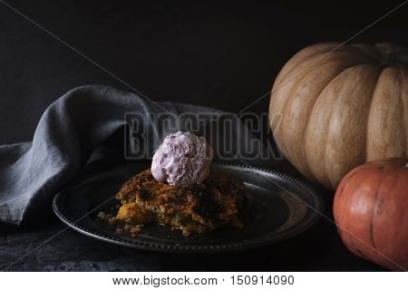 Pumpkin dump cake with ice cream on the metal plate on the stone table