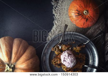 Pumpkin dump cake with ice cream on the metal plate on the stone table horizontal
