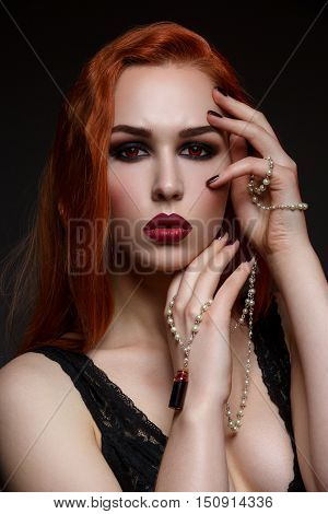 Beautiful vampire young woman with hand and mouth covered in blood. Beauty shot. Bright makeup.