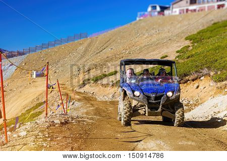SOCHI RUSSIA - OCTOBER 31 2015: Sports mountain ATV Quad Bike with passengers coming down the mountain. Hills and peaks of Caucasus mountains. Krasnaya Polyana - Alpine ski resort constructed from 2003 to 2011 for Sochi games. Rosa Khutor Sochi Russia