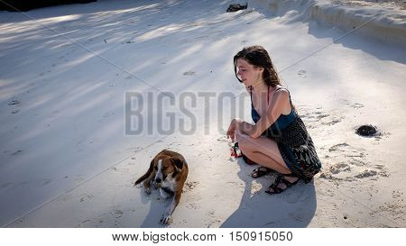 Girl with long wet hair and dog sitting on the ocean beach sand best friends