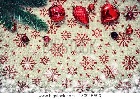 Red Christmas ornaments cones heart balls and xmas tree on canvas background with red glitter snowflakes. Xmas card. Happy New Year. Space for text