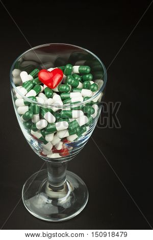 Glass of pills vitamins. Drugs in a glass container on a black background. Nutritional supplements for athletes. Diet concept.