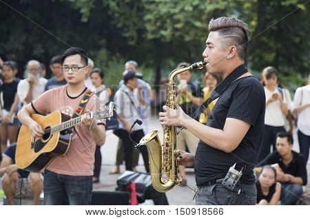 Hanoi, Vietnam - Oct 8, 2016: Asian street musician performing with their instruments on a weekend walking street around Hoan Kiem lake and tourist audience in the background.